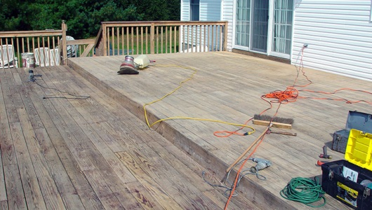 The bulk of the old sealer has been stripped off. We are now buffing and sanding the deck.