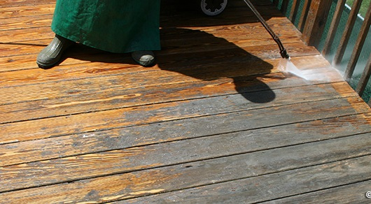Photo of power washing and stripping a deck.