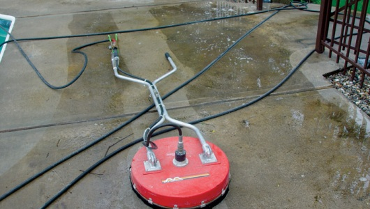 Concrete cleaning with a hot water surface cleaner.