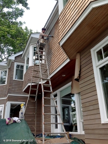 Oiling cedar house using a 40 foot ladder.