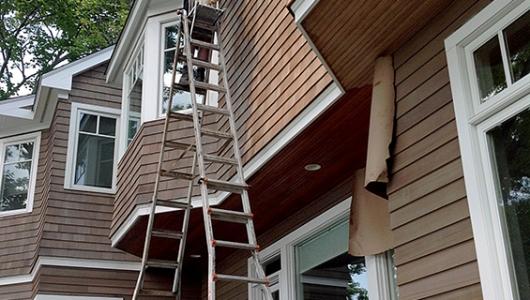 Oiling cedar house using a 40 foot ladder.